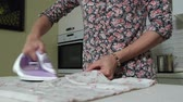ütüleme : woman ironing a mountain of laundry at home in the kitchen