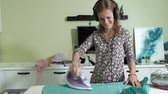 prasowanie : woman ironing the mountain of laundry at home in the kitchen listening to music on headphones and dancing