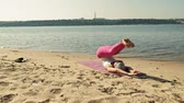 размышлять : Old retired woman doing some yoga on the beach super slow motion