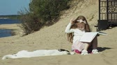 excitação : A sweet girl sits on the sand and reads a book strokes a dog