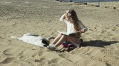 инсультов : A sweet girl sits on the sand and reads a book strokes a dog
