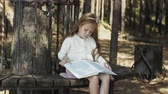 totyogó kisgyerek : A sweet girl sits in the woods and reads a book Stock mozgókép