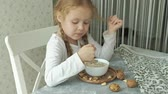 eats : Little cute girl eats oatmeal with nuts and dried fruits for breakfast. Healthy food concept Stock Footage