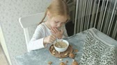 뮤 즐리 : Little cute girl eats oatmeal with nuts and dried fruits for breakfast. Healthy food concept 무비클립