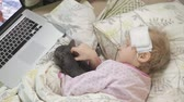 termômetro : Sick girl with a temperature. A child with fever is lying in bed with a cat.