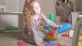 berçário : Lovely laughing little kid, preschool blonde, playing with colorful toys, sitting on the floor in the room