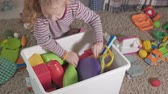 školka : Lovely laughing little kid, preschool blonde, playing with colorful toys, sitting on the floor in the room