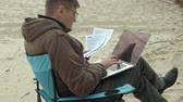 not defteri : Mature businessman sitting and relaxing near a river. Man in a warm jacket and using laptop. Stok Video
