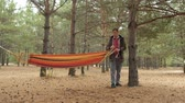 hamak : A young man in the forest sets a hammock