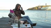 док : man and girl, father and daughter, sit in the river port, drink tea, picnic, laugh, in warm clothes Стоковые видеозаписи