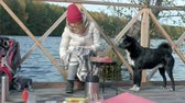 вещи : Woman tourist in warm clothes on the bridge by the river bank with a backpack, preparing sausages on the grill, picnic, sitting next to a dog, active leisure, healthy lifestyle. Travel concept