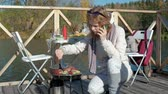 et suyu : young woman in warm clothes, prepares vegetables and meat on the grill, uses the phone, a picnic on the river bank on a wooden bridge, a weekend, cold weather, camping, tourism