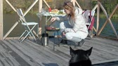 wood grill : young woman in warm clothes, preparing vegetables and meat on the grill, preparing a burger, a dog playing nearby, a picnic on the river bank on a wooden bridge, a weekend, cold weather, outdoor recreation, tourism