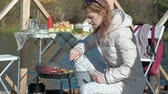 margem do rio : young woman in warm clothes, preparing vegetables and meat on the grill, preparing a burger, a dog playing nearby, a picnic on the river bank on a wooden bridge, a weekend, cold weather, outdoor recreation, tourism