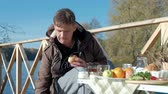 wood grill : mature man, in warm clothes, sitting at the table, eating, pouring tea from a bottle, picnic on the river bank on a wooden bridge, weekend, cold weather, outdoor recreation, tourism Stock Footage