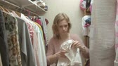 guarda roupa : Beautiful girl smiles and goes through hangers with clothes in her dressing room