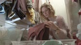 szafy : A beautiful girl smiles, sorts and folds the clothes in the baskets in her dressing room. puts things in order Wideo