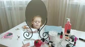 забавный : little girl with red hair looks in the mirror, cleans the skin of the face with wet wipes, make-up, face, fashion, style, cosmetics