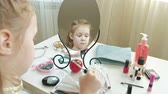 corar : a little girl with red hair puts on a concealer, looks in the mirror, makeup, face, fashion, style, cosmetics