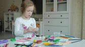 plasticina : happy little girl plays with plasticine, rolls balls with her hands, figures and color pencils lie on the desktop, development of fine motor skills of hands