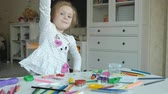 plasticina : happy little girl plays with plasticine, sculpts a figure, on the desktop are figures and colored pencils, the development of fine motor skills of hands Stock Footage