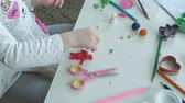 пластилин : happy little girl plays with plasticine, sculpts a figure, on the desktop are figures and colored pencils, the development of fine motor skills of hands Стоковые видеозаписи