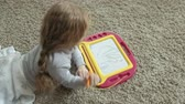 conhecimento : A little girl with red wavy hair lies on the floor and draws on a magnetic board. The concept of the educational process.