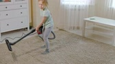 yardım : a little girl with blond hair cleans up with a vacuum cleaner, brings order and cleanliness, helps mom Stok Video