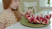 granátové jablko : happy little girl with blond hair eats pomegranate, healthy food concept, close-up portrait