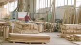 плотничные работы : a man saws wooden door blanks on the machine, the production of village interior doors