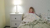 pajamas : little girl in bed playing on tablet
