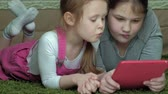 pre teen : girls sisters playing on the tablet in the room, web surfing, rest