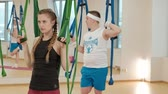 postoj : Aerial, antigravity yoga in gym. Group of people swinging in the hammocks