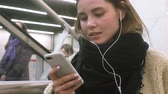 エスカレーター : young brunette woman uses a phone with headphones