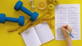 weights : sports calendar, healthy food, shooting on a yellow background top view