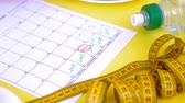 závaží : Keeping a fitness calendar.concept of healthy food, diet, top view, yellow background