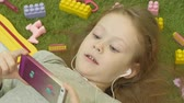 spielwaren : little girl lying on a green background in headphones and using a phone, top view