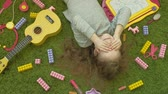 toys : little girl laughs lying on green background, top view Stock Footage