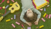 inocente : little girl laughs lying on green background, top view Vídeos