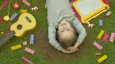 próximo : little girl laughs lying on green background, top view Stock Footage