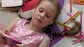 短剣 : little girl lying on the floor uses the phone, listens to music 動画素材