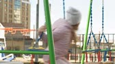 playground : little girl riding on a swing, spring