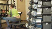 does : The overweight man does squats with squats with a weight disc for a barbell. Fitness training. Healthy lifestyle concept Stock Footage