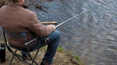 senta : Mature man catches fish on the river.
