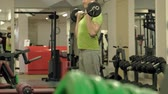 A overweight man lifts an ez barbell while standing at the gym. Exercise for biceps. Fitness. Healthy lifestyle.
