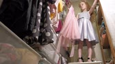 wieszak : Beautiful little girl chooses dress in home wardrobe. Beauty and fashion