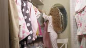 escolher : Beautiful little girl chooses dress in home wardrobe. Beauty and fashion