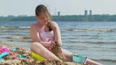 школьница : Girl builds a sand castle on the river bank Стоковые видеозаписи
