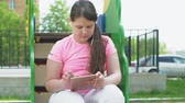 latta : Children use a computer tablet, walk on the playground Filmati Stock