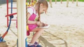 próximo : preschool girl use mobile devices outdoors Stock Footage